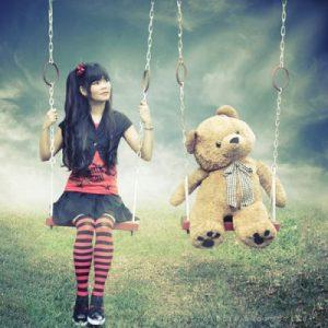 Girl and teddy swinging